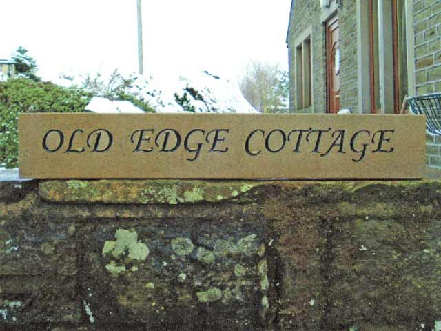 Carved stone house sign