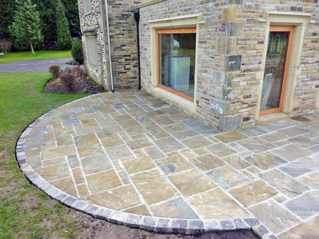 A patio with a mix of sizes and colours of riven yorkstone flags